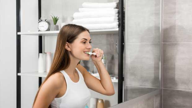 Dívka si čistí zuby před umývadlem