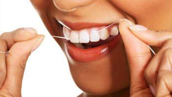 Žena si čistí zuby dentální nití